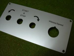 Gravure de flèches pour indiquer la rotation avec pré-perçage pour les boutons.