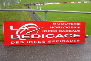 Panneau publicitaire La Dédicace avec logo pour un terrain de football.