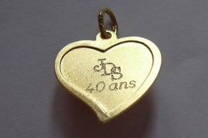 Initiales gravés sur un pendentif en or.