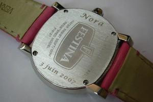 Marquage laser d'un prénom et d'une date de naissance sur le fond d'une montre.