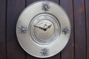Gravure sur assiette avec horloge intégrée avec quatre edelweiss en étain.