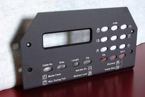 Pièce en laiton trouée et marquée au laser de l'utilité des différents boutons.