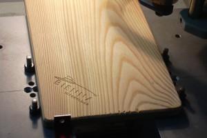 Gravure d'un logo et de texte sur une planche en bois.